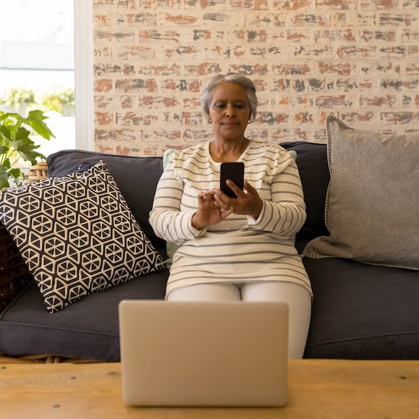 Front view of an active African American senior woman using mobile phone while sitting on a sofa in living room at home